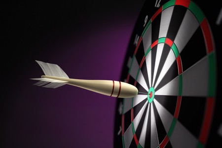 A classic wooden dart stuck on the bullseye of the dartboard