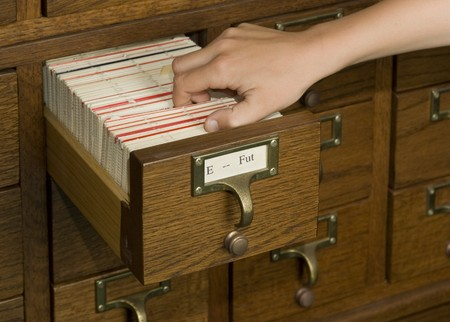 Hand reaching into a card catalog file drawer photo