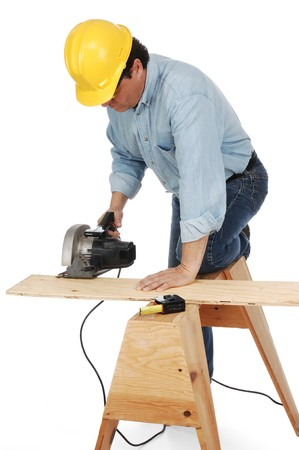 horse collar: Carpenter wearing hard hat cutting a plank on a saw horse with a power saw.