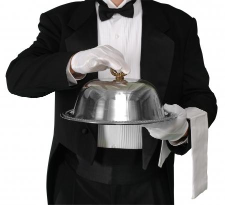 Camarero con bandeja a punto de levantar la plata cúpula de hostelería, aislada en blanco