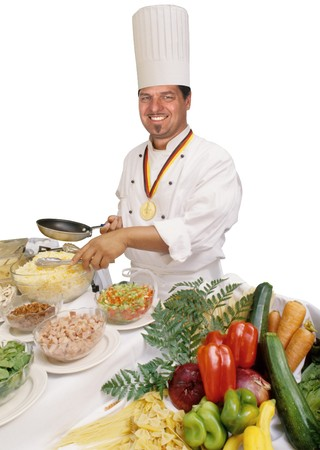 ingredient: Master chef wearing culinary medal, holding pan while standing in front of a host of ingredients