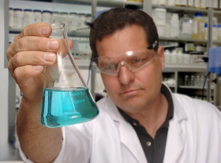 Chemist holding erlenmeyer flask containing blue chemical 版權商用圖片 - 9519796