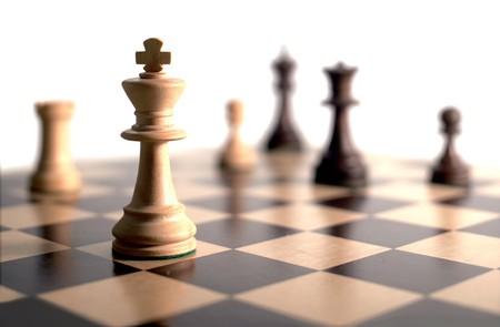 gamesmanship: piezas de ajedrez a bordo - fondo blanco  Foto de archivo