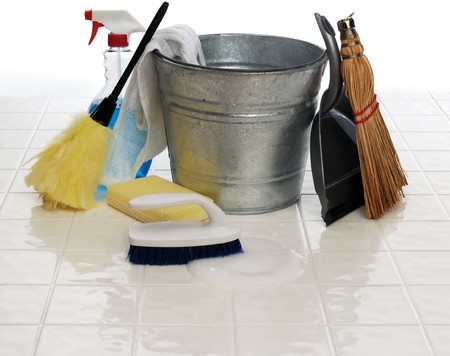 cleaning services: cleaning supplies: spray bottle, broom, duster, wash cloth, scrub brush, bucket, dust pan on white tiles Stock Photo