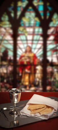 jesus christ communion: communion chalice and bread with stained glass window in the background