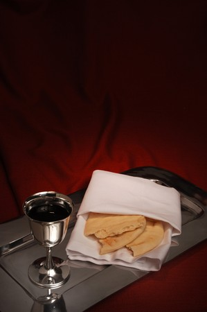 communion cup and bread on red fabric photo
