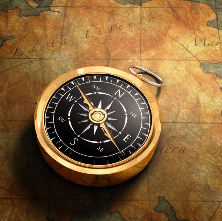 ir�ny: An old fashoned brass compass on a Treasure map background