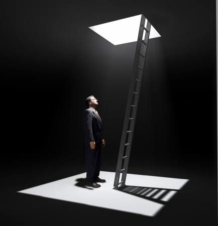 A man standing in a pit looking up to the ladder that leads out in to the light. photo