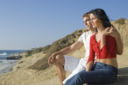 Attractive, young couple sitting on the bluffs overlooking the Pacific Ocean Stock Photo