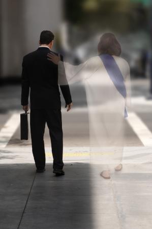 Dubbele blootstelling van een zakenman lopen de straat met Jezus aan zijn zijde