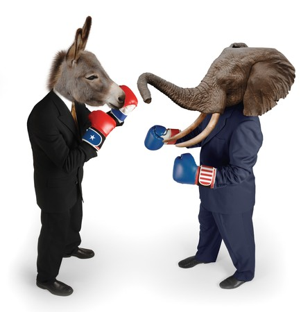 elections: US Republican and Democrat mascots represented by a donkey and an elephant face off in business suits with red white and blue boxing gloves on white background