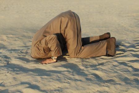 business man with his head buried in the sand Stock Photo