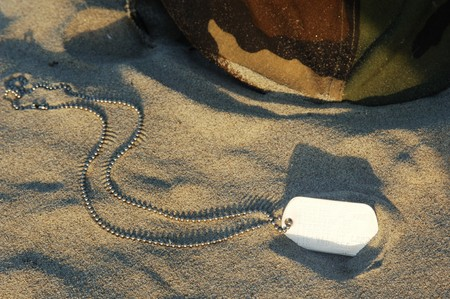 dog tag and helmet in sand photo