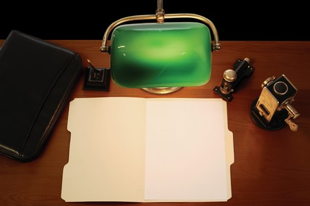 lamp: desktop with lamp, pen, briefcase, stapler, pencil sharpener and an open manila file folder with a blank letter-sized sheet of paper