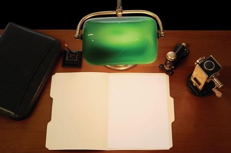 grapadora: escritorio con l�mpara, l�piz, malet�n, grapadora, sacapuntas un abierto manila archivo y carpeta con una hoja en blanco tama�o carta de papel  Foto de archivo
