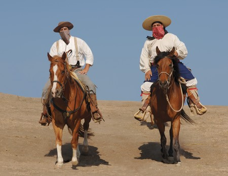 outlaws: Two banditos riding on horses