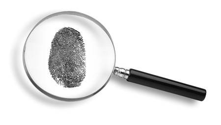 magnifying glass and thumb print on white background photo