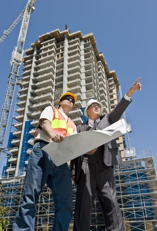 Developer and construction foreman looking over blueprints of a hirise construction project photo
