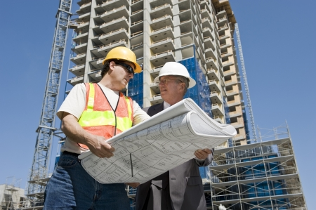 the job site: Contraente e sviluppatore di edificio discutere i progressi su un progetto di costruzione di hirise al luogo di lavoro Archivio Fotografico