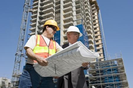 supervisores: Contratista y desarrollador de edificio discuten el progreso en un proyecto de construcci�n de hirise en el lugar de trabajo