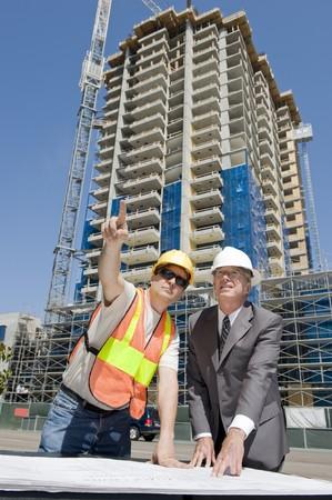 the job site: Sviluppatore di edificio sorvegliando la costruzione di un hirise con il caporeparto della costruzione in luogo di lavoro
