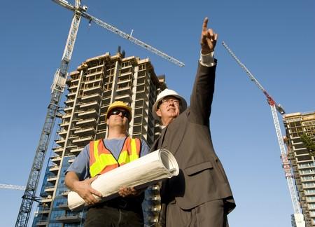 supervisi�n: Contratista y foreman en el lugar de trabajo con la construcci�n de hirise en segundo plano