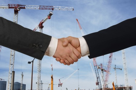developers: Two men shaking hands in front of a major construction site