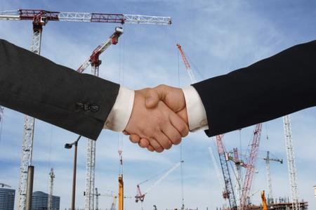Zwei Männer Händeschütteln vor der großen Baustelle