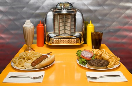 americana: 1950s style diner table with juke box, malt, cola, hot dog and hamburger.  ISTOCK: THE SONG TITLES AND BAND NAMES IN THE JUKE BOX ARE BOGUS CREATIONS BY THE ARTIST. Stock Photo