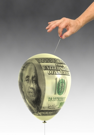 balloon printed with a hundred dollar bill about to be popped by a hand holding a hat pin Foto de archivo