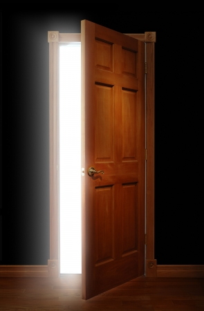 Door opening with bright light illuminating a dark space photo