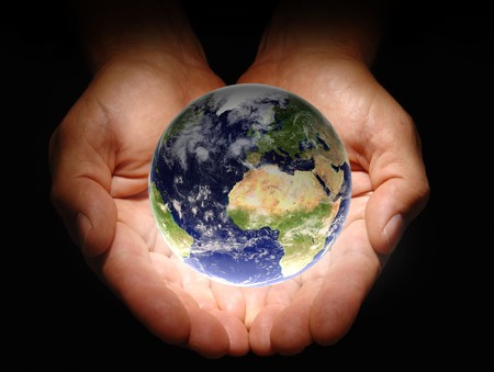 Hands holding the earth on a black background photo