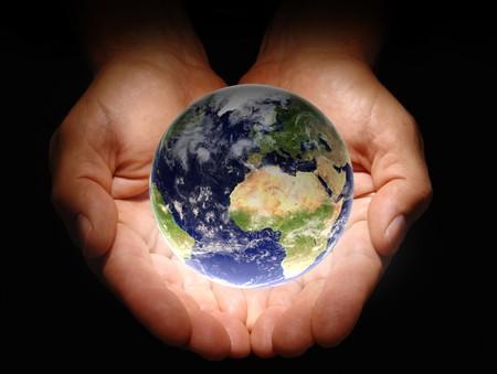 creador: Manos sosteniendo la tierra sobre un fondo negro