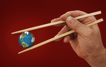 devouring: hand holding the earth between two chopsticks on Chinese red background