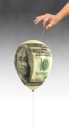 Balloon mapped with a 100 Dollar bill about to be popped with a straight pin