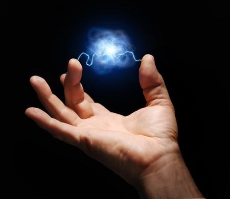 elektriciteit: mannenhand met elektriciteit vonkontlading tussen duim en middelvinger met plasma bal opgeschort in het midden Stockfoto