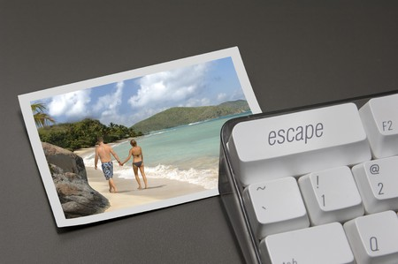escape key: close up of escape key on a computer keyboard with a photo of a tropical paradise next to it Stock Photo