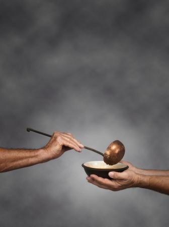 gente pobre: Composici�n vertical de un hombre sosteniendo un taz�n en ambas manos, recibiendo una raci�n de sopa de otro hombre sosteniendo un cuchar�n de sopa