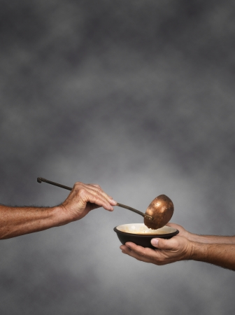 poor man: Vertical composition of a man holding a bowl in both hands, receiving a serving of soup from another man holding a soup ladle Stock Photo