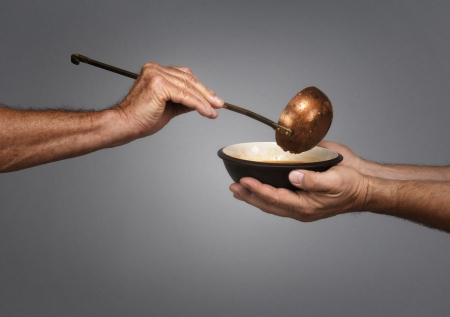 to feed: man holding a bowl in both hands, receiving a serving of soup from another man holding a soup ladle