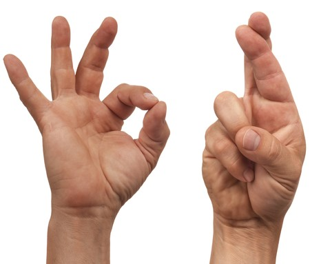 two male hands making the OK and fingers crossed sign