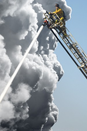 fireman helmet: A Fire Man on a lift up high hosing a fire below him Stock Photo