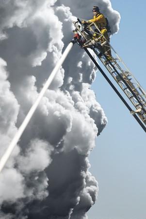 bombero de rojo: Un hombre de fuego en un ascensor alto ejemplos un incendio por debajo de �l Foto de archivo