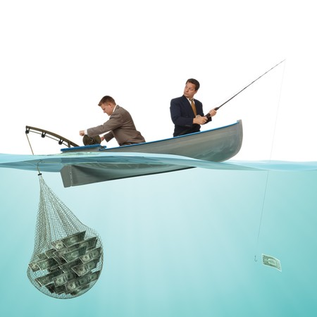 2 buisness men on a small fishing boat fishing money out if the sea from a split view of a under and above water profile. Stock Photo