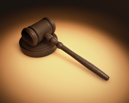 defendant: A Judges gavel being lite in a spotlight with an overall antique fashon