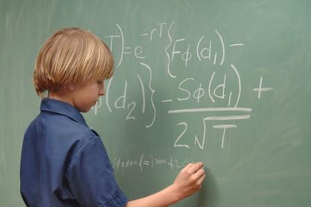 Negen éénjarigenjongen die geavanceerde wiskunde op een bord doet Stockfoto