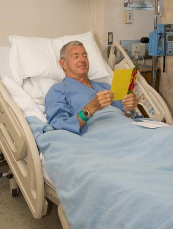 Hombre en la cama de hospital leer bien tarjeta get Foto de archivo