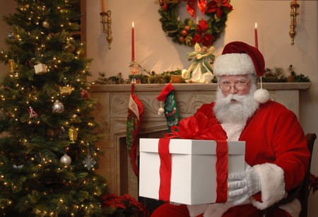 Santa next to a Christmas tree giving a gift Stock Photo