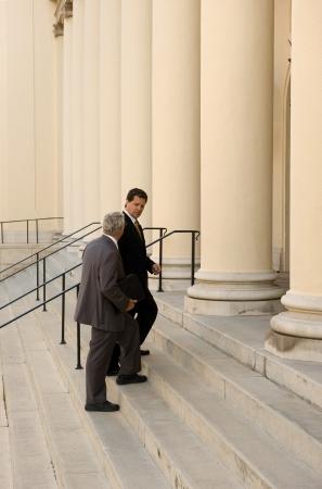 abogado: Abogado y cliente caminar hasta los pasos de un Palacio de justicia Foto de archivo