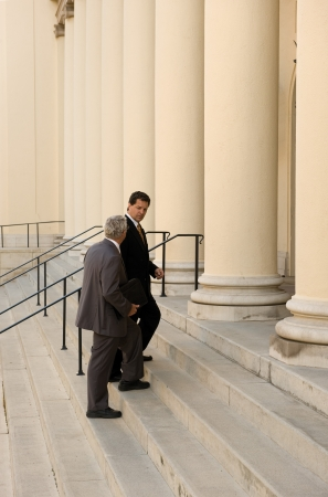 defendant: Attorney and client walking up the steps of a courthouse Stock Photo